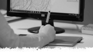 Greyscale image with person writing in front of computer.