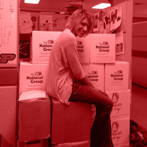 Red gradient map image of employee on boxes.