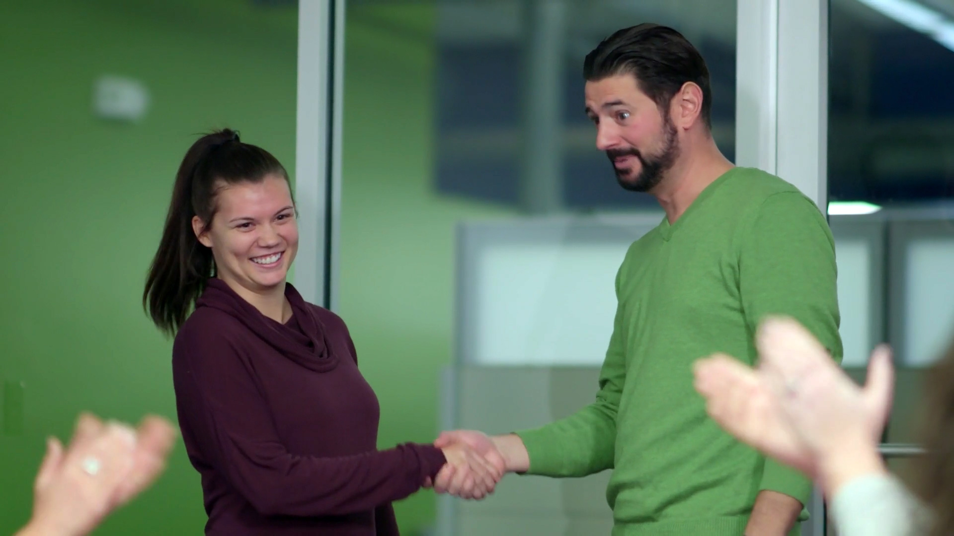 SDI Innovations employees shaking hands at meeting.